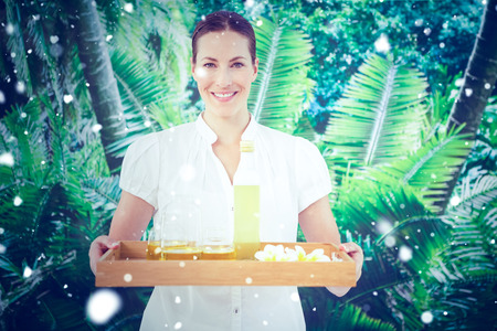beauty therapist: Snow against smiling beauty therapist holding tray of beauty treatments