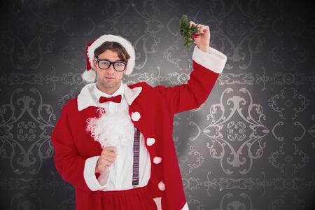 patterned wallpaper: Geeky hipster in santa costume holding mistletoe   against elegant patterned wallpaper in grey