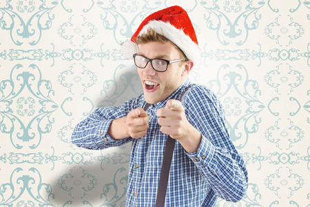 patterned wallpaper: Geeky hipster wearing santa hat against elegant patterned wallpaper in blue and cream