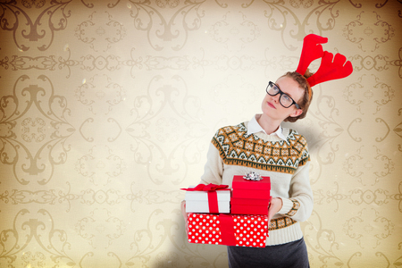 patterned wallpaper: Thoughtful geeky hipster holding presents  against elegant patterned wallpaper in neutral tones Stock Photo
