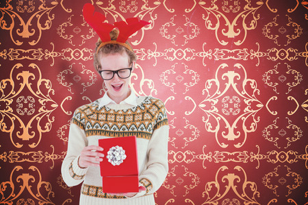 patterned wallpaper: Surprised geeky hipster opening present against elegant patterned wallpaper in red and gold