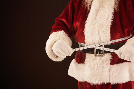 background brown: Santa Claus measures his belly against dark brown background