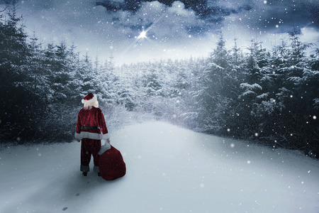 snow falling: Santa carrying sack of gifts  against snow scene Stock Photo