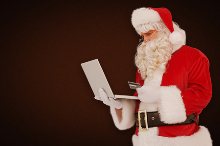 online shopping: Santa claus shopping online with laptop  against white background with vignette