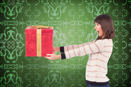 patterned wallpaper: Surprised brunette holding a gift against elegant patterned wallpaper in red and gold