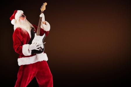 lean back: Santa playing electric guitar against dark brown background