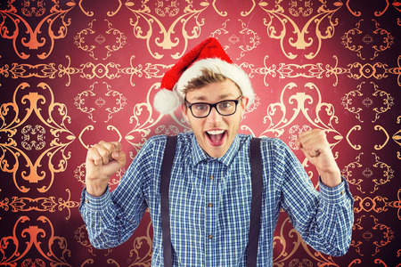 patterned wallpaper: Geeky hipster wearing santa hat against elegant patterned wallpaper in red and gold
