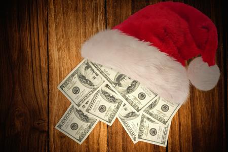 christmas savings: Hand holding hundred dollar bill against wooden table