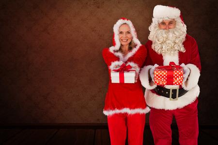 mrs: Santa y se�ora Claus sonriendo a la c�mara regalo de ofrecimiento contra el cuarto con el papel pintado Foto de archivo