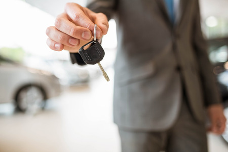 automobile dealership: Close up of businessman giving car key at new car showroom