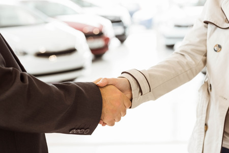 introduction: Salesman shaking a customer hand at new car showroom