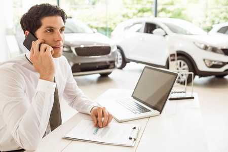 Smiling salesman having a phone call at new car showroom