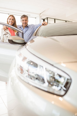 car showroom: Smiling couple leaning on car at news car showroom