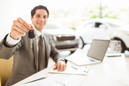 selling service smile: Smiling salesman holding a customer car key at new car showroom