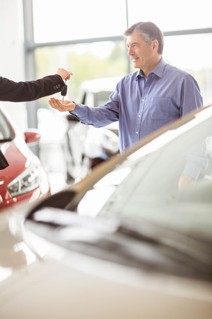 fingertips: Saleswoman giving car keys while shaking hand of a client at new car showroom Stock Photo