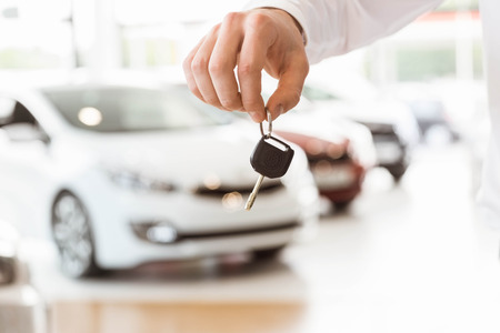 fingertips: Someone holding car keys by his fingertips at car showroom