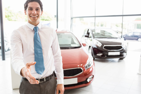 automobile dealership: Smiling businessman reaching his hand at new car showroom