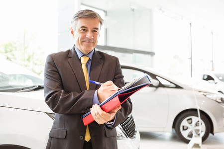 renter: Smiling salesman writing on workbooks at new car showroom