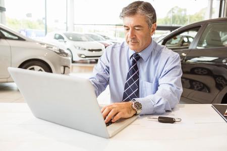 renter: Serious salesman behind his desk at new car showroom Stock Photo