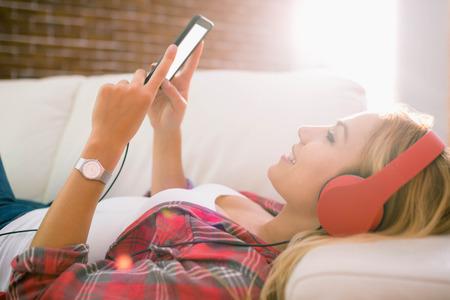 ライフスタイル: 自宅のリビング ルームのソファで音楽を聞いて非常に金髪 写真素材
