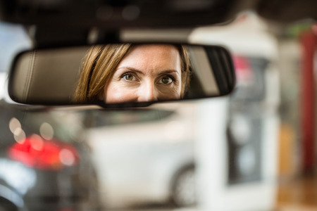 Young woman in the drivers seat looking in the mirror at new car showroom Stock Photo
