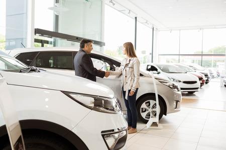 renter: Salesman shaking a customer hand at new car showroom