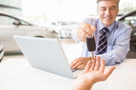 salesman: Smiling salesman holding a customer car key at new car showroom