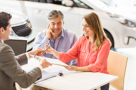Smiling couple buying a new car at new car showroom Stock Photo