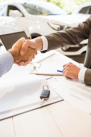 reach customers: Salesman shaking a customer hand at new car showroom