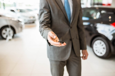 selling service smile: Close up of salesman giving a customer car keys at new car showroom