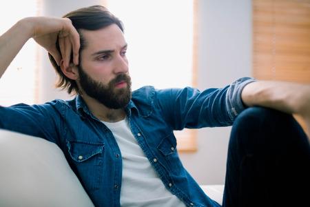nerveux: homme Unahppy réflexion sur son canapé à la maison dans le salon Banque d'images