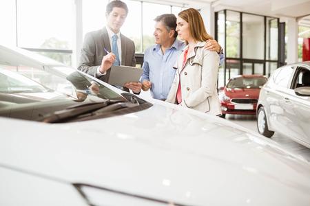 car showroom: Smiling businessman presenting a car at new car showroom