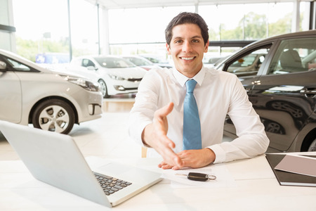 car service: Smiling salesman ready to shake hand at new car showroom Stock Photo