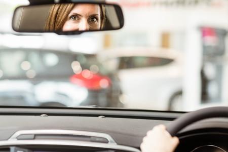 espejo: Mujer joven en el asiento del conductor mirando en el espejo en la nueva exposici�n de coches Foto de archivo