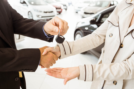 automobile dealership: Salesman offering car key to a customers at new car showroom