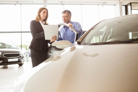undersign: Smiling businesswoman undersign a car contract at new car showroom