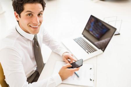 Smiling salesman having a phone call at new car showroom