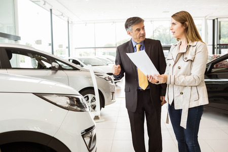 renter: Salesman showing a car to a client at new car showroom Stock Photo