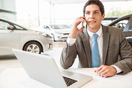 telephone call: Smiling salesman having a phone call at new car showroom