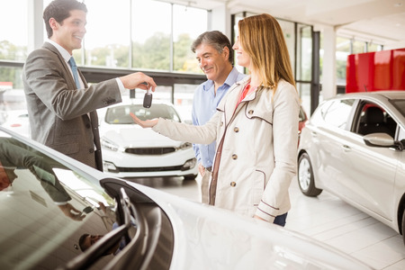 together with long tie: Salesman giving car key to a couple at new car showroom Stock Photo