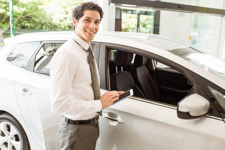 automobile dealership: Smiling salesman using tablet near a car at new car showroom Stock Photo