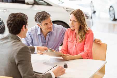 automobile dealership: Smiling couple buying a new car at new car showroom Stock Photo