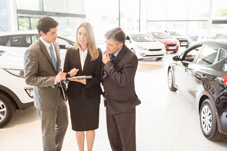automobile dealership: Sales team look at a clipboard at new car showroom