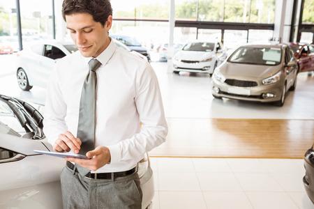 salesman: Smiling salesman using tablet near a car at new car showroom Stock Photo