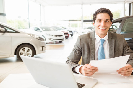 salesman: Smiling salesman reading a document at new car showroom Stock Photo