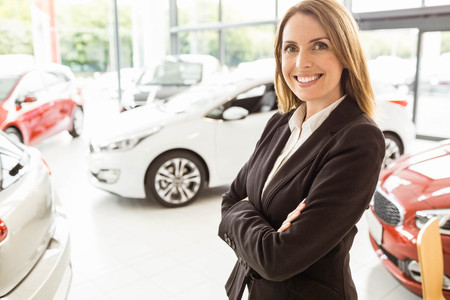 car showroom: Smiling saleswoman standing with arms crossed at new car showroom Stock Photo
