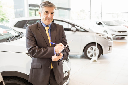 renter: Portrait of a salesman with clipboard at new car showroom