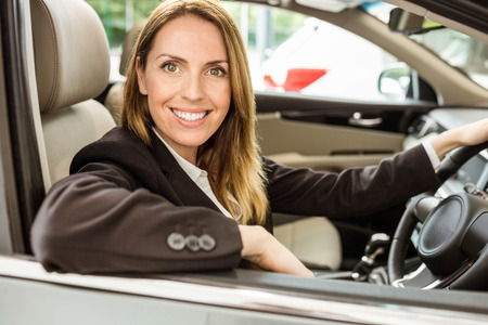 siting: Smiling businesswoman siting in a car at new car showroom