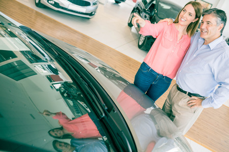 looking for work: Couple talking together while looking at car at new car showroom