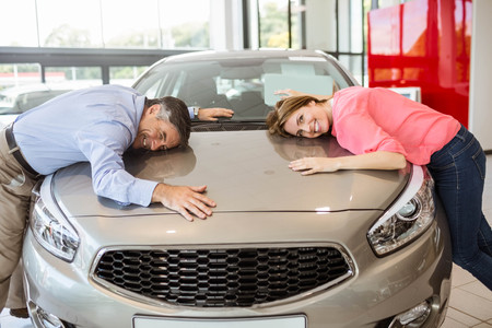 hugging: Casual smiling couple hugging their new car at new car showroom